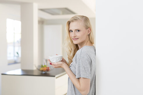 Smiling blond woman with cup of coffee in kitchen - SHKF000646