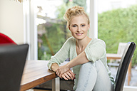 Portrait of smiling blond woman sitting at dining table - SHKF000661