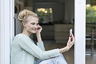 Blond woman sitting at terrace door holding cell phone - SHKF000664