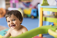 Portrait of baby boy playing in children's room - JASF001098