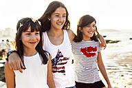 Three happy girls on the beach at sunset - MGOF002264