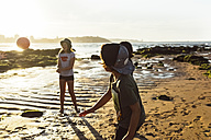 Kids playing with a ball on the beach at sunset - MGOF002279