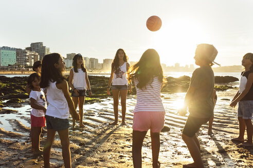 Kids playing with a ball on the beach at sunset - MGOF002282