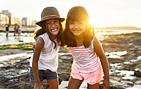 Portrait of two smiling girls on the beach at sunset - MGOF002309