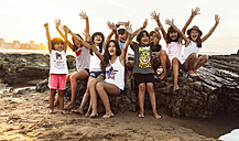 Group of happy kids sitting on rock on the beach at sunset - MGOF002312