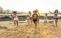 Kids running on the beach at sunset - MGOF002315