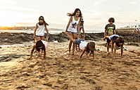 Kids playing on the beach at sunset - MGOF002318