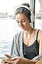 Smiling young woman listening music with headphones looking at her cell phone - TAMF000566