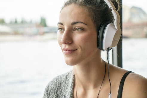 Portrait of relaxed woman listening music with headphones - TAMF000569