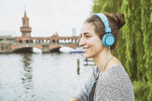 Germany, Berlin, relaxed woman listening music with headphones - TAMF000572