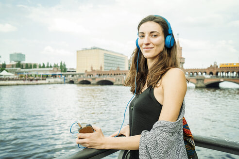 Germany, Berlin, portrait of relaxed woman listening music with headphones - TAMF000575