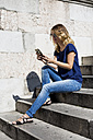 Smiling blond woman sitting on stairs looking at cell phone - MAUF000838