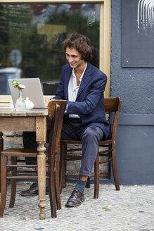 Smiling young businessman working with laptop at sidewalk cafe - TAMF000586