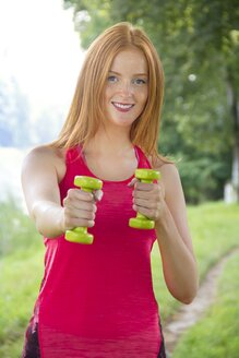 Portrait of smiling athlete holding dumbbells - YFF000564