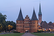 Germany, Luebeck, Town gate Holstentor and Church of St. Peter at dusk - PCF000261