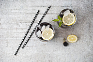 Blackberry limonade with lemon and ice cubes in glasses - MYF001747
