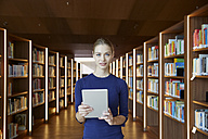 Portrait of young woman holding tablet in library - FMKF003040