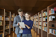 Young man and woman using tablet in library - FMKF003043