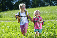 Two girls with backpacks plucking flowers in meadow - LBF001458