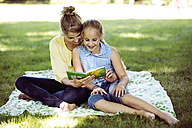 Girl and young woman sitting on blanket in a park reading book - GDF001117