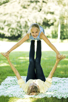 Young woman in a park balancing girl on her legs - GDF001120