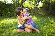 Two sisters having fun ogether on a meadow - LVF005213