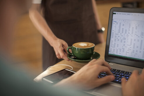 Waitress serving coffee to man in a cafe working on laptop - ZEF009850