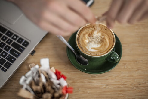 Hand pouring sugar into cup of cappuccino next to laptop - ZEF009853