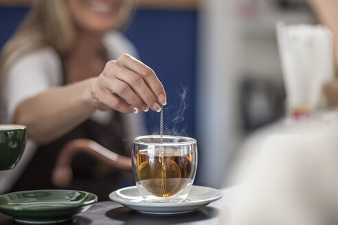 Woman in a cafe preparing glass of tea - ZEF009856