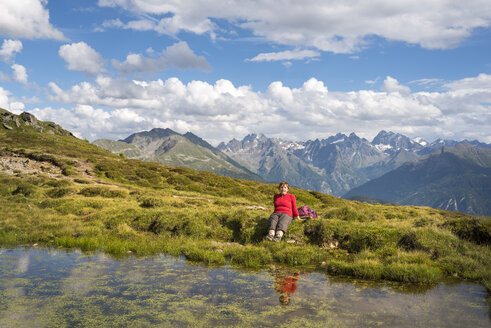 Woman hiking in the Alps, resting at lake - MKFF000327