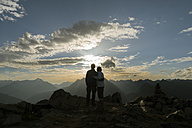 Happy couple watching sunset in the mountains - MKFF000330
