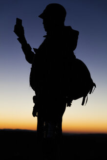 Silhouette of hiker looking at smart phone - MIDF000787