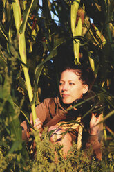 Woman hiding in cornfield and watching something with binoculars - MIDF000790