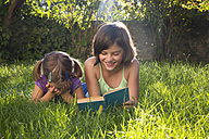 Girl on a meadow reading out book to her little sister - LVF005227