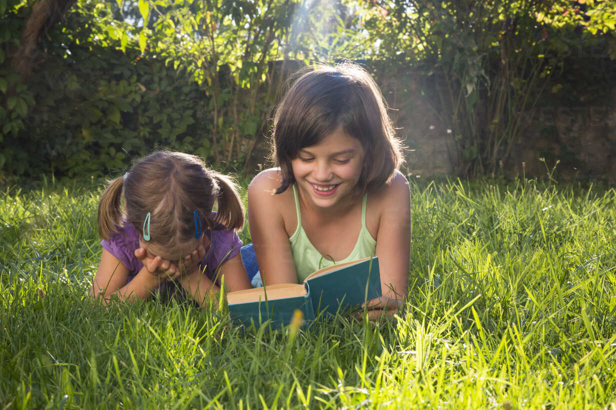 Girl on a meadow reading out book to her little sister - LVF005227 - Larissa Veronesi/Westend61