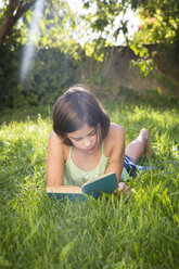 Girl reading book on a meadow - LVF005230