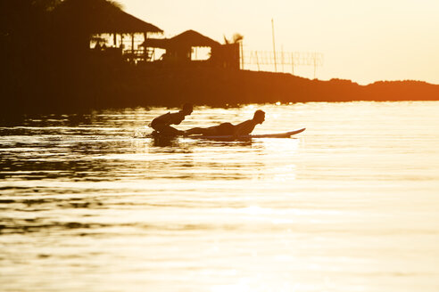 Thailand, couple doing yoga on paddleboard at sunset, cobra pose - SBOF000172