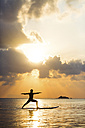 Thailand, man doing yoga on paddleboard at sunset, bridge position, warrior pose - SBOF000178