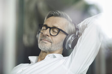 Portrait of man with eyes closed listening music with headphones - SBOF000199