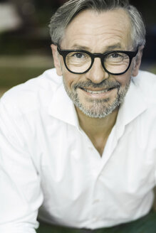 Portrait of smiling man with grey hair and beard wearing spectacles - SBOF000205