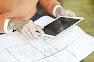 Man with tablet and construction plan, partial view - SBOF000220