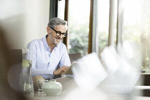 Man sitting in living room using tablet - SBOF000235