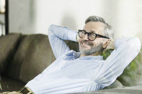 Portrait of smiling man relaxing on the couch - SBOF000244