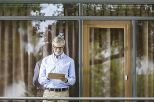 Man standing on balcony of his house looking at tablet - SBOF000247