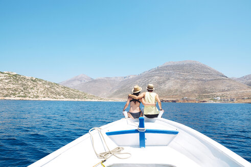 Greece, back view of couple sitting arm in arm on bow of a boat looking at Amorgos Island - GEMF000991
