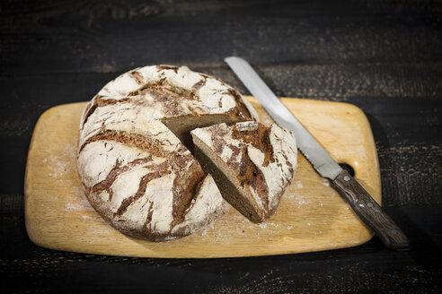 Rustic rye bread on chopping board - MAEF011983