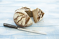 Rustic rye bread on blue wood, knife - MAEF011986