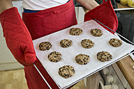 Woman showing a tray of freshly baked cookies - ABZF001034