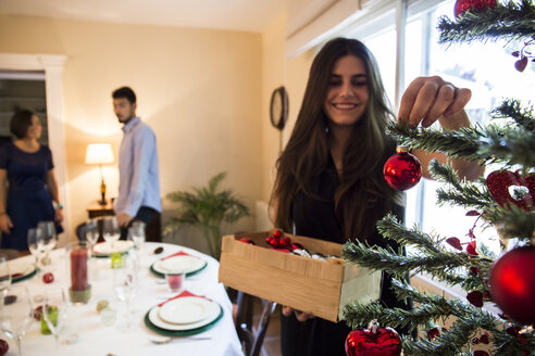 Woman decorating the Christmas tree with friends in background - ABZF001037