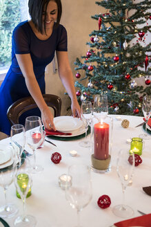 Woman setting the table for Christmas dinner - ABZF001046